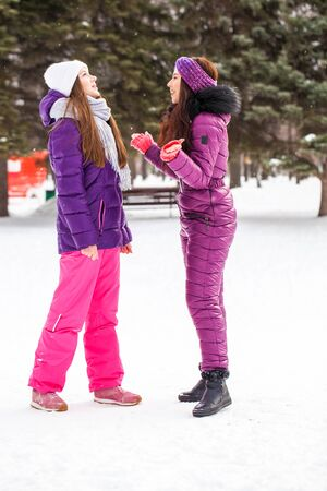 Full-length portrait of two young beautiful girls in ski suit posing in winter in the park