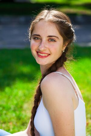 Closeup portrait of a young beautiful brunette woman in on summer park background