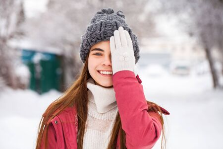 Portrait of a young beautiful girl in a red winter jacket posing in the winter outdoors