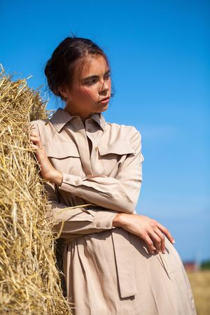 Young beautiful brunette woman in a beige dress posing on a background of haystacks in a cut field