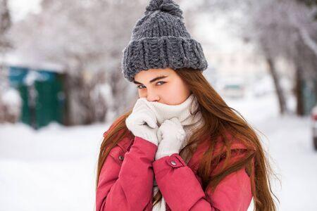 Porträt eines jungen schönen Mädchens in einer roten Winterjacke, die im Winter draußen posiert Standard-Bild