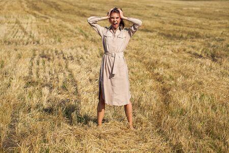 Ganzkörperporträt junges schönes brünettes Mädchen in einem beigefarbenen Kleid, das vor dem Hintergrund eines gemähten Weizenfeldes posiert