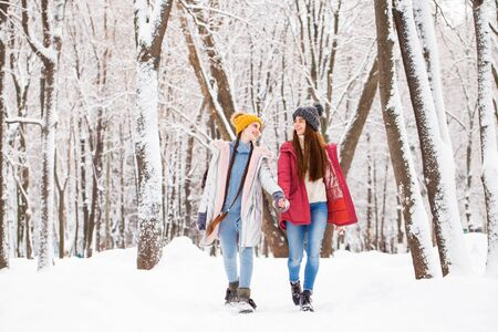 full-length portrait two young beautiful girlfriends walk in the winter park