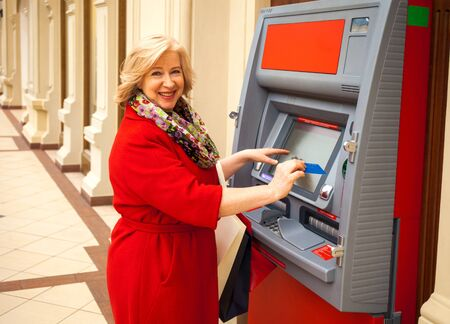active pensioner withdraws cash from an ATM
