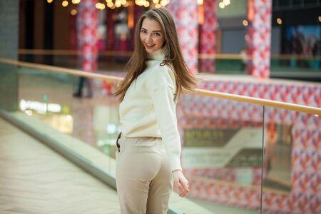 Portret młodej pięknej dziewczyny nastolatka w beżowym swetrze i spodniach pozowanie w centrum handlowym Zdjęcie Seryjne
