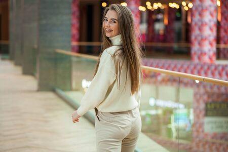 Porträt eines jungen schönen Teenager-Mädchens in beigefarbenem Pullover und Hosen, die im Einkaufszentrum posieren