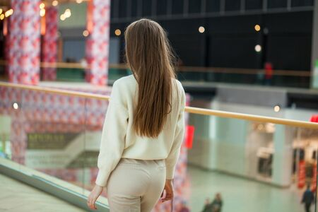 Portrait of a young beautiful teenager girl in beige sweater and pants posing in the mall