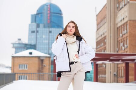 Portrait of a young beautiful teenager girl in a white down jacket and beige pants posing outdoors in winterk Stock Photo