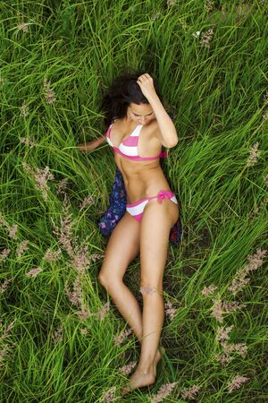 Young beautiful sexy girl in a red bathing suit lying on the grass top view Reklamní fotografie
