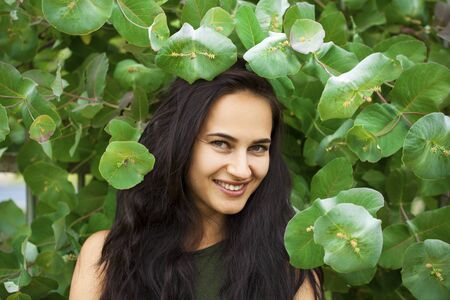 Portrait of a young beautiful woman in green foliage