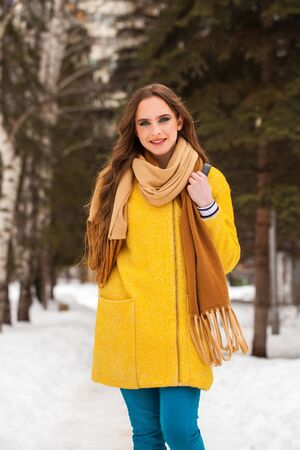 Portrait of a young beautiful teenager girl in yellow coat walking winter park Stock Photo