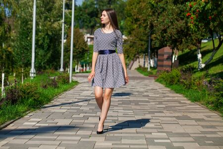 Portrait in full growth, young beautiful brunette woman in a gray dress walking on the street, summer embankment outdoors Stock Photo