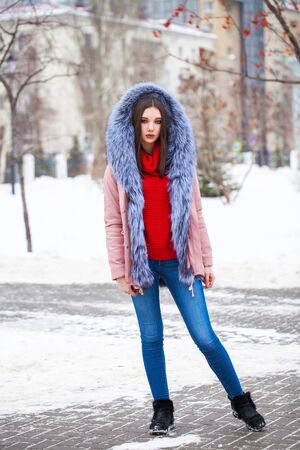 Full-length portrait of a young beautiful woman in blue jeans and fur jacket posing in the winter outdoors Stock Photo