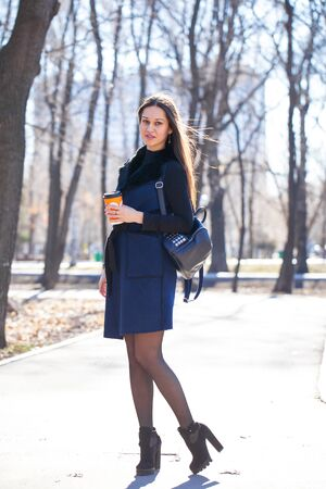 Portrait of a young beautiful woman in blue coat walking spring park Stock Photo