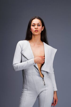 Sexy fashion brunette woman in gray leather suit posing in the studio on a gray background