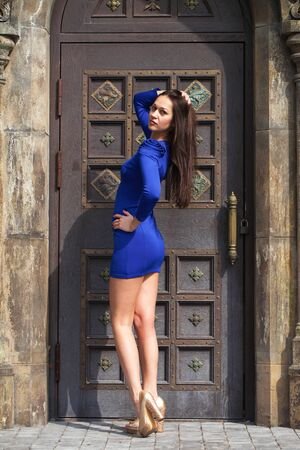 Full-length portrait young beautiful brunette woman in blue dress posing against the backdrop of an old castle in the Gothic style