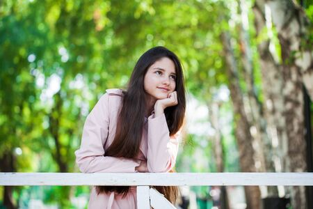 Portrait of a young beautiful brunette girl in pink coat on a background of autumn park Banque d'images