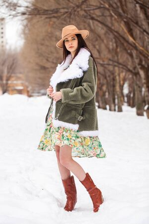 Portrait of a young beautiful teenager girl in winter park
