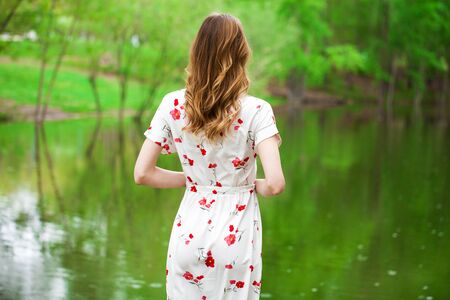 Hair back view. Close up young blonde woman in white dress posing by the lake