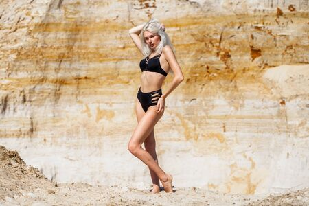 Portrait of a young beautiful blonde girl in black bikini posing on a sand pit background