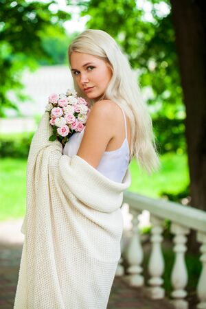 Closeup portrait of a young blonde girl with a bouquet of pink flowers in summer park Stock Photo