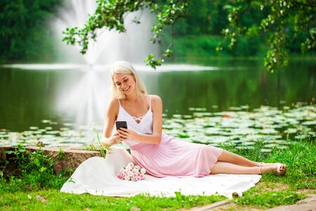 Full-length portrait of a young woman resting near a pond in a summer park Stock Photo