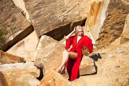 Close up portrait of a young beautiful blonde girl in black bikini and red tunic