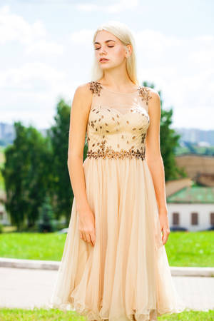 Portrait of a young beautiful blonde woman in beige dress