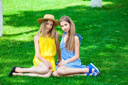 Full length portrait of two young business girls, summer street outdoors