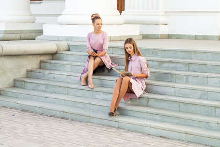 Two young female students in a pink dress are sitting on the steps