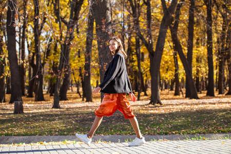 Full body portrait of a young brunette woman in orange skirt walking in autumn park