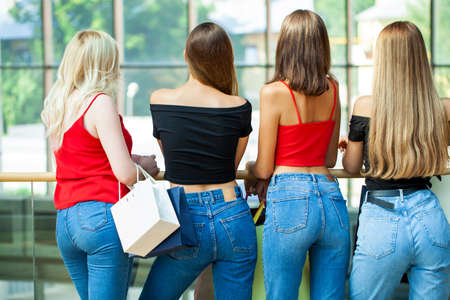 Five young girlfriends are walking in the mall with shopping