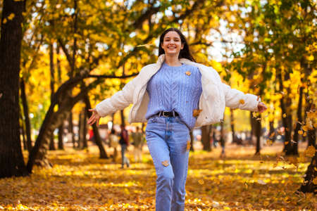 Young beautiful girl in a purple sweater lies on fallen autumn leaves