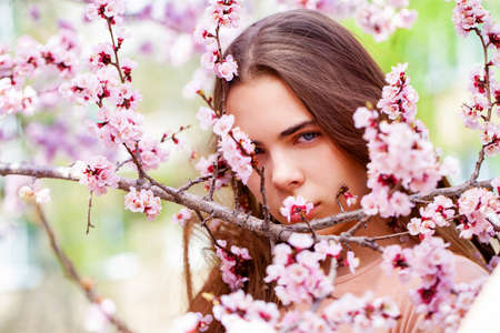 Pretty teen girl are posing in garden near blossom cherry tree with white flowers. Spring time