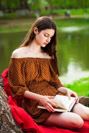 Young beautiful girl with a book resting in a summer park