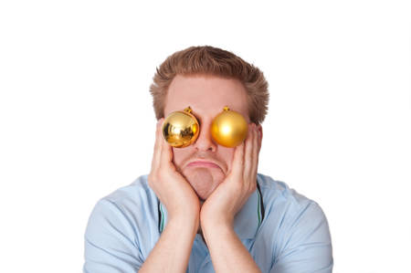 distressful: Funny image: Stressed, disappointed, frustrated young man with christmas baubles leaning his face on his hands in front of a white background