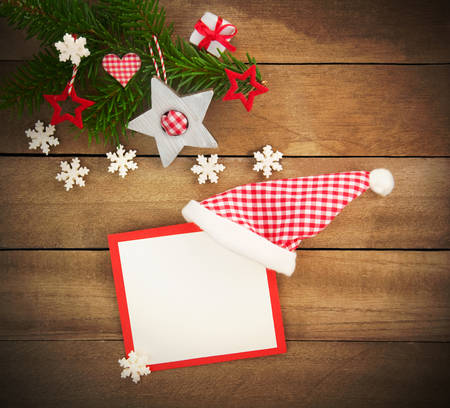 country style: Rustic brown wooden background decorated with green fir branch, red and red and white checkered stars and santa hat with christmas card, gift and snowflakes as christmas decoration in Country Style