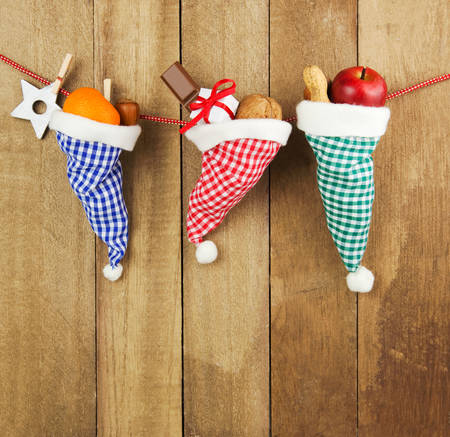 tatty: Three checkered santa hats filled with christmas gifts, nuts, chocolate and fruits hanging in front of a rustic wooden wall