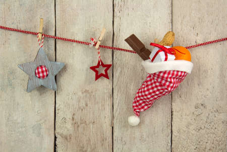 stocking cap: Red and white checkered Santa hat filled with nuts, fruits, candy and a gift hanging on a red line in front of a bright wooden background with Stars decoration Stock Photo