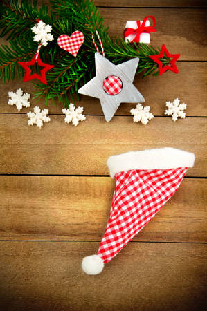 fir branch: Rustic brown wooden background decorated with green fir branch, red and red and white checkered stars and santa hat, gift and snowflakes as christmas decoration in Country Style Stock Photo