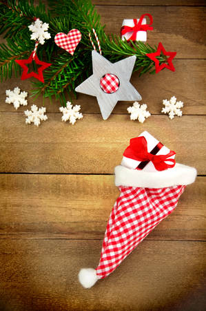 country style: Rustic brown wooden background decorated with green fir branch, red and red and white checkered stars and santa hat, gift and snowflakes as christmas decoration in Country Style Stock Photo