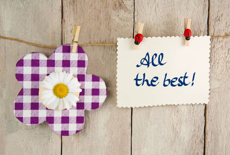 best message: violet checkered decoration flower with chamomile and tag with all the best message hanging on a ribbon in front of a wooden backdrop