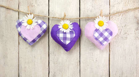 marguerites: Three violet hearts with marguerites hanging on a ribbon in front of wooden background
