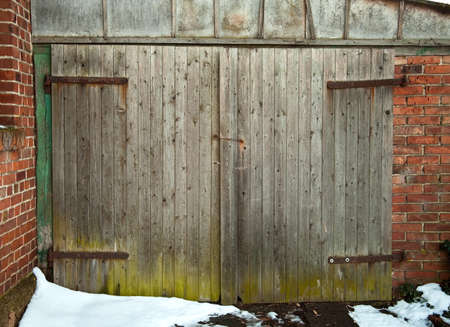 verdigris: old wooden barn door with green base and snow Stock Photo