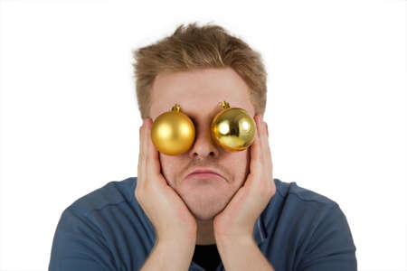 distressful: Funny image: Stressed, disappointed, frustrated young man with Christmas baubles leaning his face on his hands in front of a white background Stock Photo