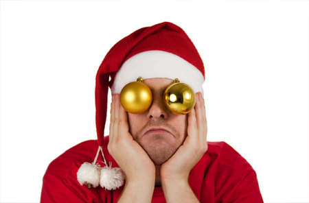 Funny picture with sad frustrated stressed disappointed young Santa Claus with Christmas tree balls as eyes with face resting on his hands isolated on white background Stock Photo