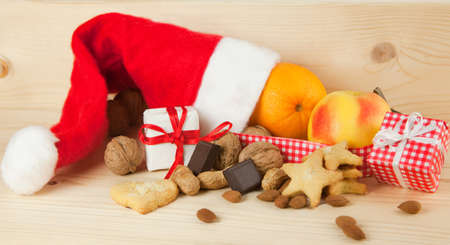 Christmas fruits and Nicholas gift consisting of a Santa Claus hat with cookies, biscuits, walnuts, hazelnuts, almonds, oranges, apples, chocolate, gifts and Christmas decoration isolated against white background