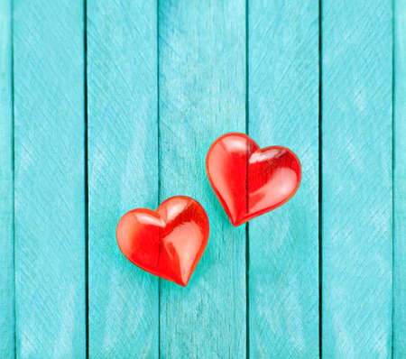 Two red hearts of glass in front of blue wooden backdrop for valentine's day
