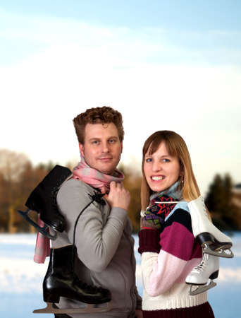iceskates: Smiling young woman and man outside on snow winter day holding ice skates outdoors Stock Photo