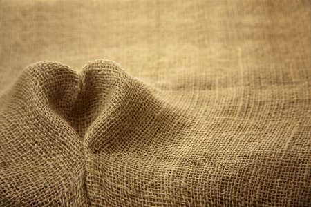 Rustic hessian fabric textile texture folded in heart shape backdrop   Imagens